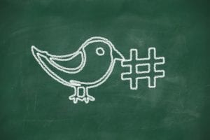 Twitter bird and a hashtag drawn on a chalkboard