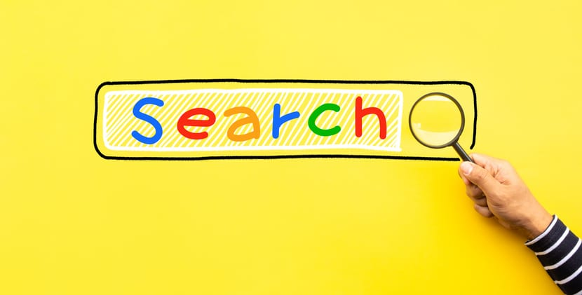 A magnifying glass examines the google search engine bar.